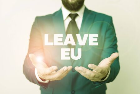 Text sign showing Leave Eu. Business photo showcasing An act of a demonstrating to leave a country that belongs to Europe Man with opened hands in fron of the table. Mobile phone and notes on the table Stock fotó
