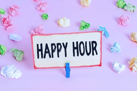 Conceptual hand writing showing Happy Hour. Concept meaning Spending time for activities that makes you relax for a while Colored crumpled papers empty reminder pink floor clothespin