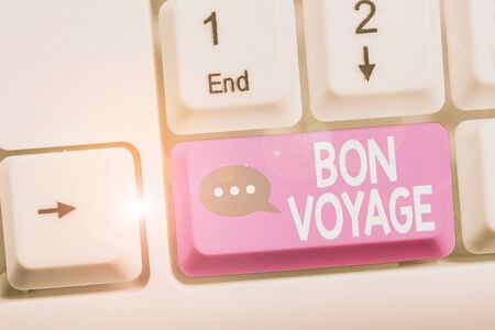 Writing note showing Bon Voyage. Business concept for used express good wishes to someone about set off on journey White pc keyboard with note paper above the white background 写真素材