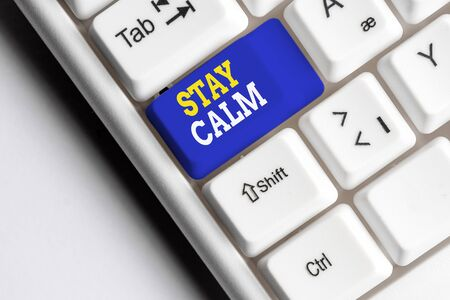 Conceptual hand writing showing Stay Calm. Concept meaning Maintain in a state of motion smoothly even under pressure White pc keyboard with note paper above the white background