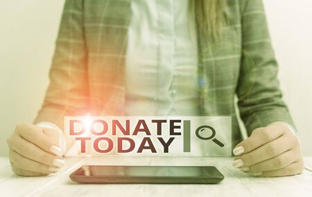 Handwriting text writing Donate Today. Conceptual photo time to give money or goods to help a demonstrating or organization Business woman sitting with mobile phone on the table