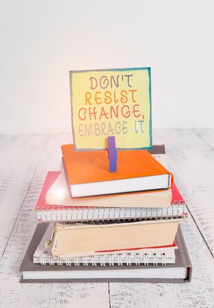 Word writing text Don T Resist Change Embrace It. Business photo showcasing Be open to changes try new things positive pile stacked books notebook pin clothespin colored reminder white wooden