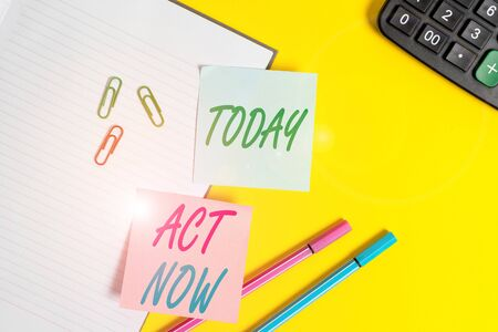 Text sign showing Act Now. Business photo showcasing Having fast response Asking someone to do action Dont delay Empty blue paper with copy space paper clips and pencils on the yellow table Stock Photo