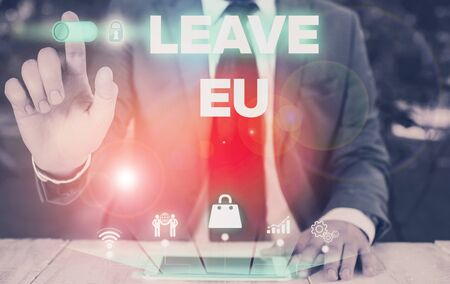 Conceptual hand writing showing Leave Eu. Concept meaning An act of a demonstrating to leave a country that belongs to Europe Male wear formal suit presenting presentation smart device