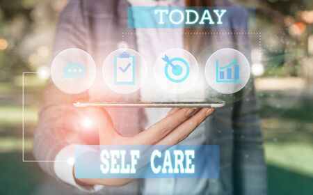 Text sign showing Self Care. Business photo showcasing Give comfort to your own body without professional consultant Female human wear formal work suit presenting presentation use smart device
