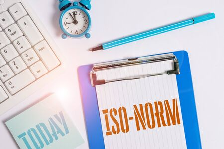 Writing note showing Iso Norm. Business concept for An accepted standard or a way of doing things most showing agreed Flat lay above table with clock pc keyboard and copy space note paper Stock Photo
