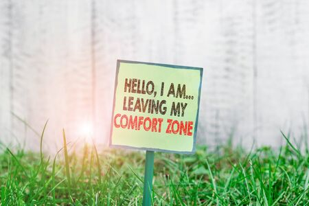 Conceptual hand writing showing Hello I Am Leaving My Comfort Zone. Concept meaning Making big changes Evolution Growth Plain paper attached to stick and placed in the grassy land