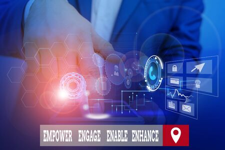 Handwriting text writing Empower Engage Enable Enhance. Conceptual photo Empowerment Leadership Motivation Engagement Male human wear formal work suit presenting presentation using smart device Banque d'images