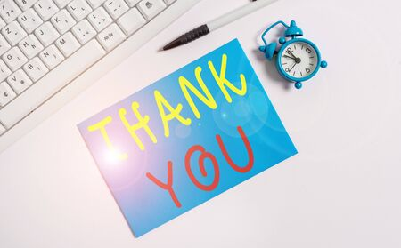 Writing note showing Thank You. Business concept for replaying on something good or greetings with pleased way Flat lay above empty note paper on the pc keyboard pencils and clock Stock Photo