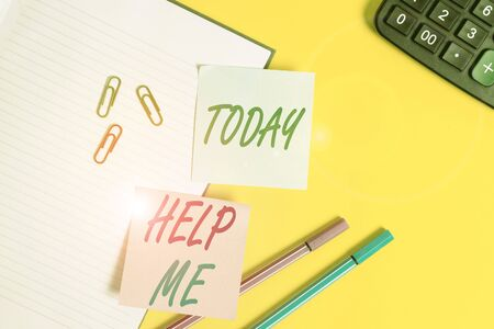 Text sign showing Help Me. Business photo showcasing Asking someone to assist you Shouting for it Teamwork Volunteer Empty blue paper with copy space paper clips and pencils on the yellow table