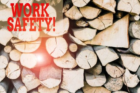 Text sign showing Work Safety. Business photo showcasing policies and procedures in place to ensure health of employees Background dry chopped firewood logs stacked up in a pile winter chimney