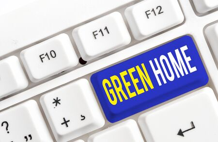 Text sign showing Green Home. Business photo showcasing An area filled with plants and trees where you can relax White pc keyboard with empty note paper above white background key copy space