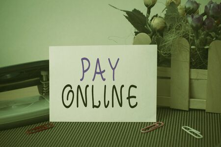 Text sign showing Pay Online. Business photo text buy products or service using credit card on any website Flowers and writing equipments plus plain sheet above textured backdrop Stockfoto