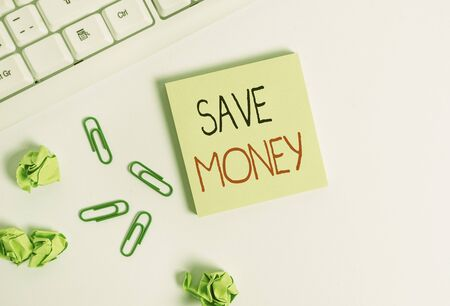 Handwriting text Save Money. Conceptual photo store some of your cash every month to use them sometime later Square empty green note paper with pencil on the white background and pc keyboard Zdjęcie Seryjne