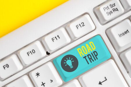 Conceptual hand writing showing Road Trip. Concept meaning Roaming around places with no definite or exact target location White pc keyboard with note paper above the white background