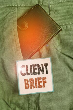 Handwriting text writing Client Brief. Conceptual photo information to be used as the basis for an advertising campaign Small little wallet inside man trousers front pocket near notation paper