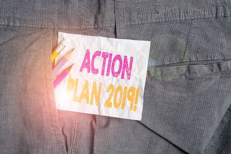 Text sign showing Action Plan 2019. Business photo showcasing proposed strategy or course of actions for current year Writing equipment and white note paper inside pocket of man work trousers