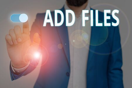 Conceptual hand writing showing Add Files. Concept meaning To put more information to a certain demonstrating,thing,or document Male wear formal suit presenting presentation smart device Stock Photo