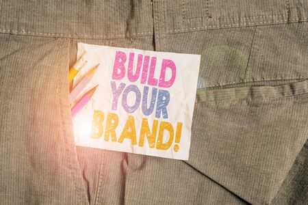 Text sign showing Build Your Brand. Business photo showcasing creates or improves customers knowledge and opinions of product Writing equipment and white note paper inside pocket of man work trousers 版權商用圖片