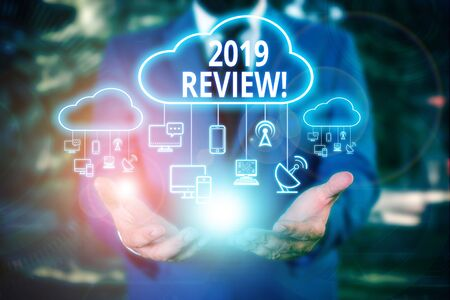 Writing note showing 2019 Review. Business concept for remembering past year events main actions or good shows Male wear formal work suit presenting presentation smart device