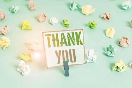 Word writing text Thank You. Business photo showcasing replaying on something good or greetings with pleased way Colored crumpled papers empty reminder blue floor background clothespin