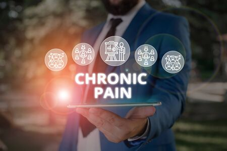 Word writing text Chronic Pain. Business photo showcasing pain that is ongoing and usually lasts longer than six months Male human wear formal work suit presenting presentation using smart device Фото со стока