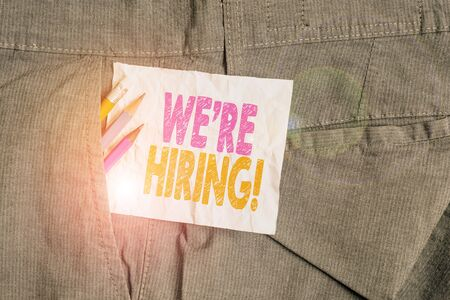 Text sign showing We Re Hiring. Business photo showcasing recently employ someone or pay someone to do particular job Writing equipment and white note paper inside pocket of man work trousers