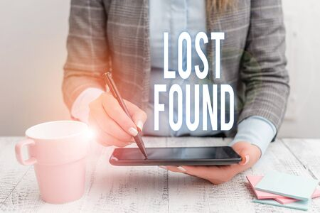 Writing note showing Lost Found. Business concept for Things that are left behind and may retrieve to the owner Business woman sitting with mobile phone and cup of coffee on the table