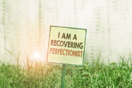 Conceptual hand writing showing I Am A Recovering Perfectionist. Concept meaning Obsessive compulsive disorder recovery Plain paper attached to stick and placed in the grassy land Stock fotó