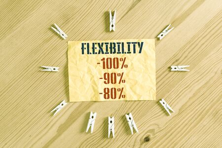 Writing note showing Flexibility 100 Percent 90 Percent 80 Percent. Business concept for How much flexible you are maleability level Colored clothespin papers empty reminder wooden floor background office