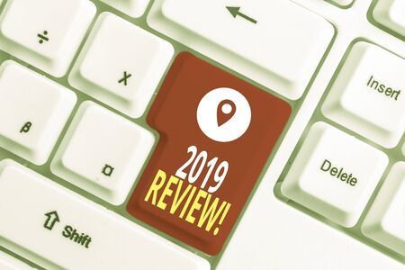 Writing note showing 2019 Review. Business concept for remembering past year events main actions or good shows White pc keyboard with note paper above the white background