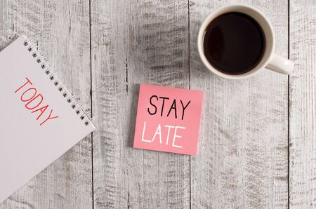 Conceptual hand writing showing Stay Late. Concept meaning A routine in which a demonstrating goes to somewhere out of time Stationary placed next to a coffee cup above wooden table