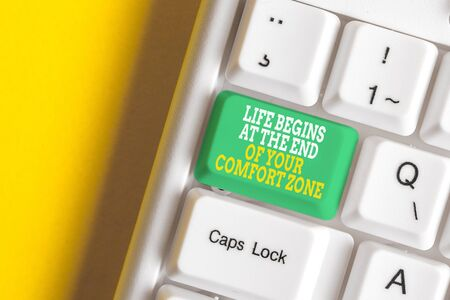 Conceptual hand writing showing Life Begins At The End Of Your Comfort Zone. Concept meaning Make changes evolve grow White pc keyboard with note paper above the white background