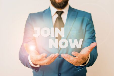 Text sign showing Join Now. Business photo showcasing An invite to a demonstrating or a friend to become a member of the group Man with opened hands in fron of the table. Mobile phone and notes on the table