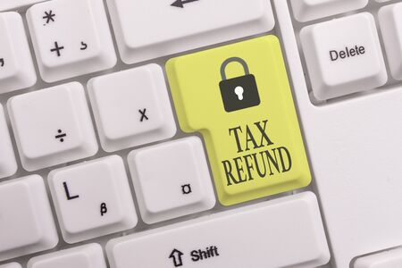 Text sign showing Tax Refund. Business photo text applied when money liability is less than the paid ones White pc keyboard with empty note paper above white background key copy space