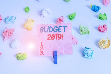 Conceptual hand writing showing Budget 2019. Concept meaning estimate of income and expenditure for current year Colored crumpled paper empty reminder white floor clothespin