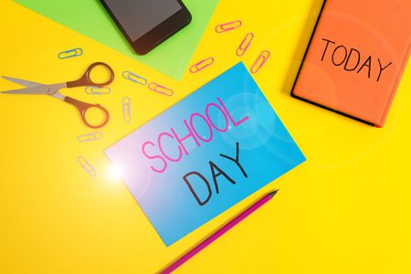 Handwriting text writing School Day. Conceptual photo starts from seven or eight am to three pm get taught there Paper sheets pencil clips smartphone scissors notebook colored background