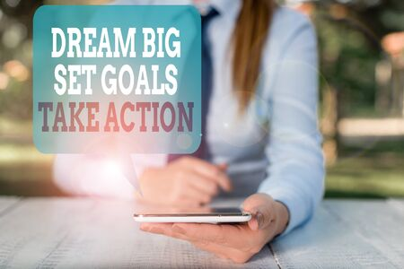 Writing note showing Dream Big Set Goals Take Action. Business concept for Motivation to follow your dreams Inspiration Female business person sitting by table and holding mobile phone 版權商用圖片