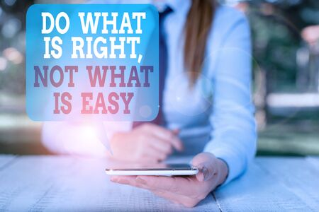 Writing note showing Do What Is Right Not What Is Easy. Business concept for Make correct actions Have integrity Female business person sitting by table and holding mobile phone