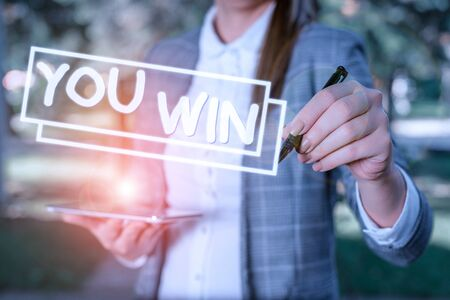 Text sign showing You Win. Business photo showcasing be first in school race or competition Got gold medal Rating Outdoor background with business woman holding lap top and pen Stock Photo