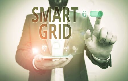 Word writing text Smart Grid. Business photo showcasing includes of operational and energy measures including meters Male human wear formal work suit presenting presentation using smart device Banco de Imagens