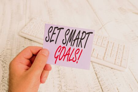 Text sign showing Set Smart Goals. Business photo showcasing list to clarify your ideas focus efforts use time wisely man holding colorful reminder square shaped paper white keyboard wood floor