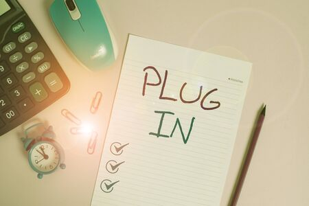 Writing note showing Plug In. Business concept for putting device into electricity to turn it on Power it Connecting Calculator clips alarm clock mouse sheet pencil colored background Banco de Imagens