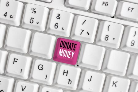 Handwriting text writing Donate Money. Conceptual photo to give money or goods to help a demonstrating or organization White pc keyboard with empty note paper above white background key copy space Stok Fotoğraf
