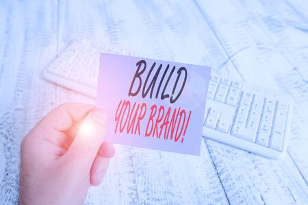 Text sign showing Build Your Brand. Business photo showcasing creates or improves customers knowledge and opinions of product man holding colorful reminder square shaped paper white keyboard wood floor Фото со стока