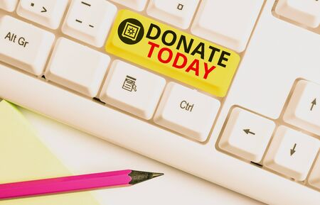Text sign showing Donate Today. Business photo text time to give money or goods to help a demonstrating or organization White pc keyboard with empty note paper above white background key copy space