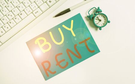 Writing note showing Buy Rent. Business concept for choosing between purchasing something or paying for usage Flat lay above empty note paper on the pc keyboard pencils and clock