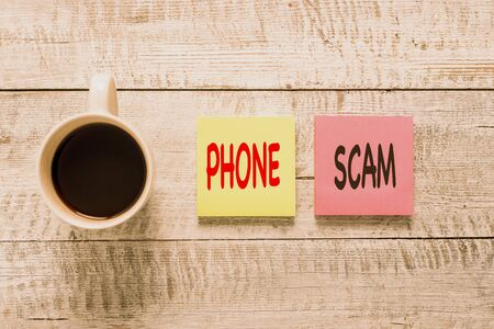 Handwriting text writing Phone Scam. Conceptual photo getting unwanted calls to promote products or service Telesales Stationary placed next to a cup of black coffee above the wooden table