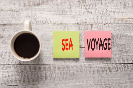 Handwriting text writing Sea Voyage. Conceptual photo riding on boat through oceans usually for coast countries Stationary placed next to a cup of black coffee above the wooden table Stockfoto