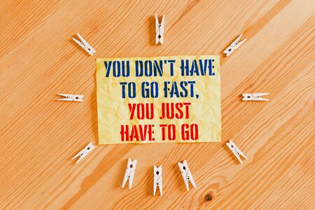 Writing note showing You Don T Have To Go Fast You Just Have To Go. Business concept for just start to reach Colored clothespin papers empty reminder wooden floor background office Stok Fotoğraf - 131365119